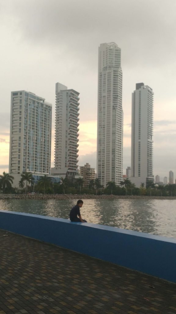 Boy sitting by pier surrounded by Modern architecture